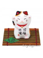 Maneki neko gatto portafortuna appoggiato su stuoia